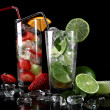 Stock Photo: Mojito cocktail with fresh limes on a black background