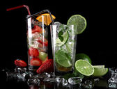 Mojito cocktail with fresh limes on a black background — Stock Photo