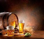 Barril de cerveza con vasos de cerveza en una mesa de madera. — Foto de Stock