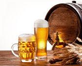 Beczka piwa z szklanki piwa na drewnianym stole. — Zdjęcie stockowe