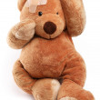 Ill teddy bear with plaster on its head. Isolated on a white background. — Stock Photo