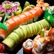 Sushi rolls on a black plate. — Stock Photo