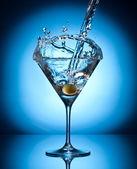Splash martini from flying olives. — Stock Photo