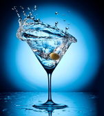 Splash martini from flying olives. — Stock Photo