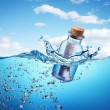 Bottle with help message floating in the see waves. - Stock Photo