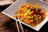 Spaghetti cinesi con gamberi su un tavolo di bambù — Foto Stock