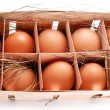 Stock Photo: Eggs with a straw in a wooden basket on a white background.