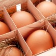 Eggs with a straw in a wooden basket - Foto Stock