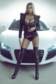 Sexy blond model in lingerie with car — Stock Photo