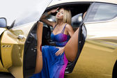The sexual blonde in car salon — Stock Photo