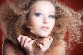 Beautiful young girl with curly hair on an orange background — Stock fotografie