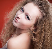 Beautiful young girl with curly hair on an orange background — Stock Photo