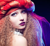Beautiful young girl with curly hair and a turban. Creative Portrait — Stok fotoğraf