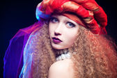 Beautiful young girl with curly hair and a turban. Creative Portrait — Stockfoto