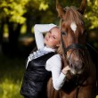 Foto Stock: Walk of beautiful young girl with horse