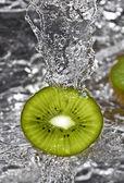 Kiwi fruit over water splashing — Stock Photo