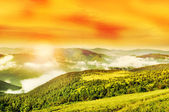 Flaring sun, golden sky and cloudy Carpathian Mountains — Stock Photo