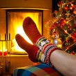 Girl resting in a home with a burning fireplace and Christmas tr — Stock Photo