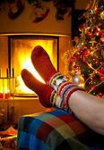 Garota descansando em uma casa com uma lareira queimando e natal tr — Foto Stock