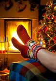 Girl resting in a home with a burning fireplace and Christmas tr — Foto Stock