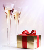 Two glasses of champagne and a gift box — Stock Photo