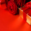 Art Valentines Day golden gift box and red roses on a red backgr — Stock Photo