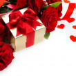 Photo: Art valentines card with red roses and gift box on white backgro