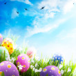 Art Easter eggs decorated with flowers in the grass on blue sky - Stock Photo