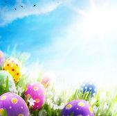 Arte huevos de pascua decoración con flores en el césped en cielo azul — Foto de Stock