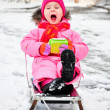 Little girl on sleigh in snowsuit — Stock Photo