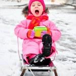 Little girl on sleigh in snowsuit — Stock Photo