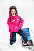 Little girl nearby sleigh in snowsuit screaming — Stock Photo