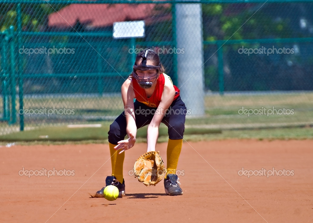 A girl catching a ground ball during a softball game.  Stock Photo #10060471