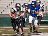 Correr com a bola de futebol da liga da juventude — Fotografia Stock