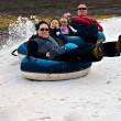 Foto Stock: Family on Snow Tubes