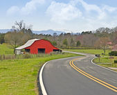 Red Barn on a Curving Road — Stock Photo