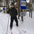 An elderly man stands on the cross-country skiing near the road signs — Stock Photo