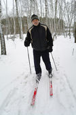 An elderly man stands on the cross-country skiing in the park in winter — Stock Photo