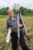 一名老翁与经纬仪测量距离领域 — 图库照片