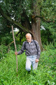 Un homme âgé avec un touriste de sac à dos va dans les fourrés de la forêt — Photo