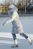 A girl in winter sports clothing on ice skates, ice skating — Stock Photo