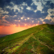 Hill with pathway and clouds on sky — Stock Photo