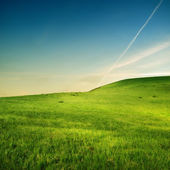 Trace of airplane over green hills — Stockfoto