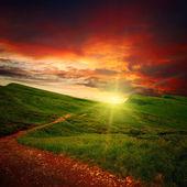 Majestuosa puesta del sol y la ruta a través de un prado — Foto de Stock