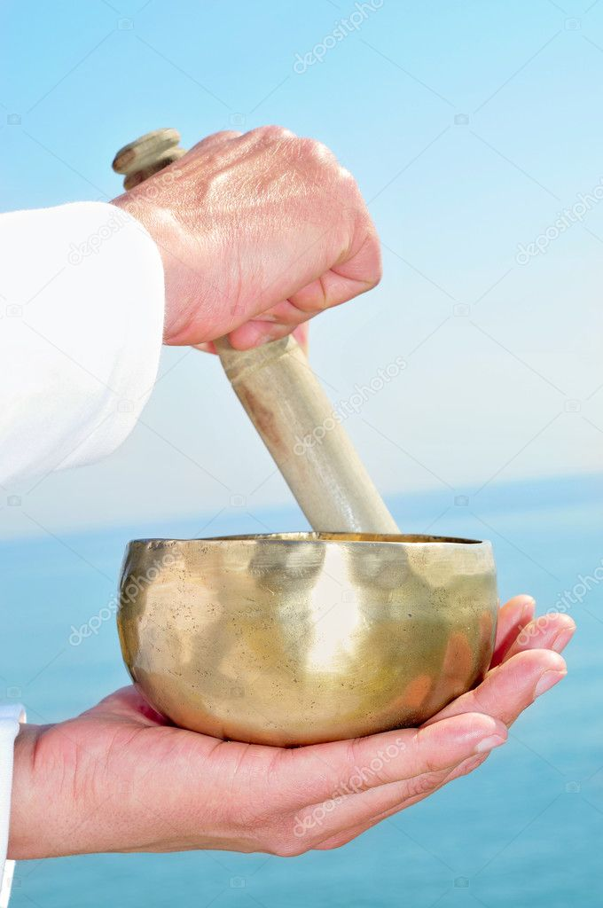Someone playing a tibetan bowl — Stock Photo #9993342