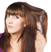 Attractive smiling woman brushing her hear — Stock Photo