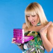 Royalty-Free Stock Photo: Happy blond girl opens a gift over blue