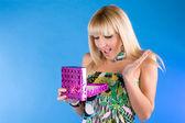 Szczęśliwy blond dziewczyna otwiera prezent na niebiesko — Zdjęcie stockowe