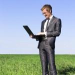 成功,自信商人绿色领域用一台笔记本电脑 — 图库照片