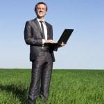 用一台笔记本电脑绿色草地上的成功、 自信商人 — 图库照片